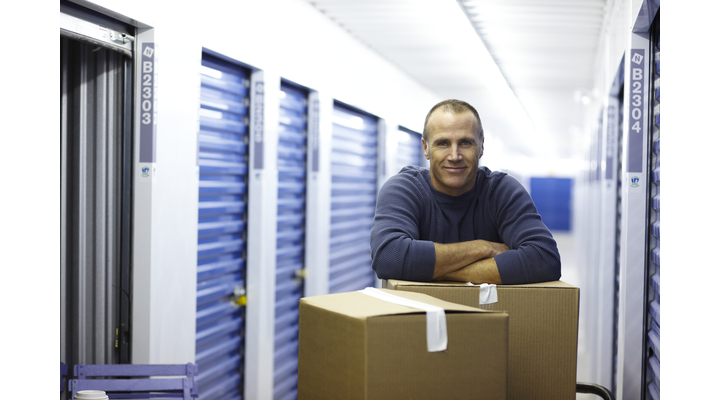 man leaning on boxes outside self storage
