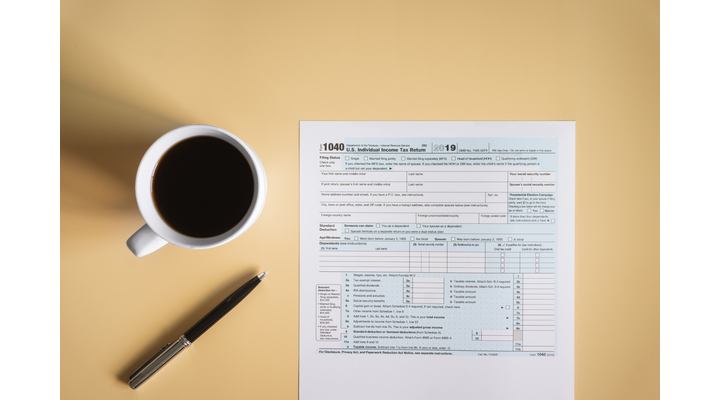 form 1040 on table with pen and coffee